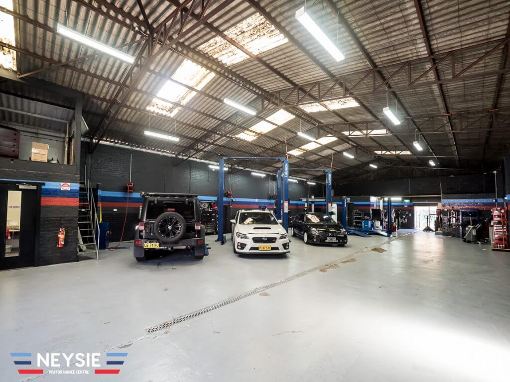 Late model cars in clean mechanic workshop.